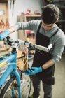 Mechanic repairing a bicycle in workshop — Stock Photo