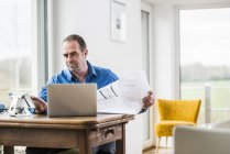 Businessman with laptop, tablet and plan at wooden table at home — Stock Photo