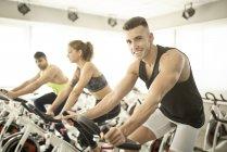 Menschen, die auf spinning Bikes im Fitness-Studio trainieren — Stockfoto