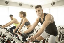 People exercising on spinning bikes in gym — Stock Photo
