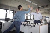 Два колеги грає в настільний футбол і даючи висока п'ять в офісі — стокове фото