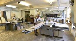 Tischler arbeitet in Werkstatt mit Holzbrettern — Stockfoto