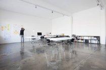 Empresário em pé na sala de conferências na parede — Fotografia de Stock