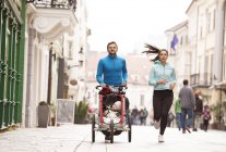 Parents running with child in stroller in the city — Stock Photo