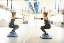Frau, training mit elektrischer Muskelstimulation vor Spiegel — Stockfoto