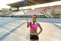 Sportswoman making selfie in race track — Stock Photo