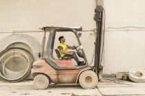 Trabalhador dirigir empilhadeira na fábrica, vista lateral — Fotografia de Stock