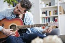 Junger Mann sitzt auf Couch und stimmt Gitarre — Stockfoto
