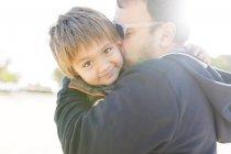 Menino nos braços de pais olhando por cima do ombro — Fotografia de Stock
