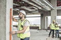 Строитель использует уровень воды на строительной площадке — стоковое фото