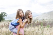 Spain, Girona, portrait of two happy sisters playing on a meadow — Stock Photo