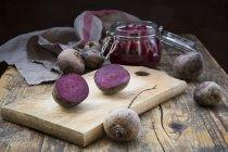 Вся і роздвоєна beetroots і консервуюча jar соління beetroots на темного дерева — стокове фото