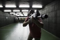 Man aiming with a tactical weapon in an indoor shooting range — Stock Photo