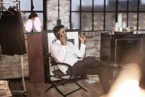 Homme détendu dans appartement parler téléphone et fumer une cigarette — Photo de stock
