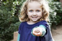 Portrait of blond little girl with a hand full of nuts — Stock Photo