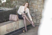 Jeune femme d'affaires, prendre une pause, assis sur un banc, pieds à friction — Photo de stock