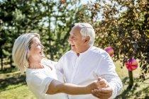 Happy elderly couple dancing outdoors — Stock Photo