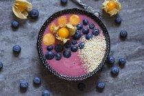 Bol de smoothie aux myrtilles avec amarant éclaté, myrtilles et physalis — Photo de stock