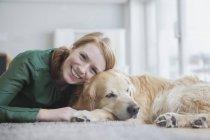 Femme couchée avec chien sur le tapis — Photo de stock