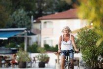 Donna anziana in bicicletta, vista frontale — Foto stock