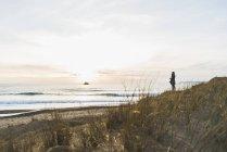 Женщина, стоящая на побережье на закате, Франция, Бретань, Финистер, полуострова Crozon — стоковое фото