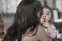 Portrait of baby girl with finger in mouth on the arms of her mother at home — Stock Photo