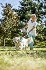 Зрелая женщина с собакой на лугу — стоковое фото