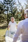 Elderly couple holding picnic blanket on a meadow — Stock Photo