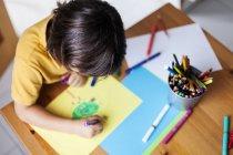 Маленький хлопчик, спираючись на жовтого паперу — стокове фото