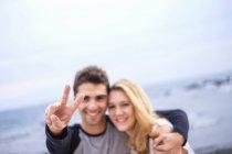 Счастливая молодая пара обнимает и делает знак победы — стоковое фото