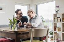 Homme âgé avec petit-fils assis à table dans le salon avec ordinateur portable et smartphone — Photo de stock