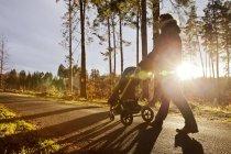 Père et fils en buggy marchant dans la forêt — Photo de stock