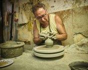 Potter in workshop working on earthenware vessel — Stock Photo