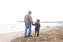 Avô e neto caminhando e conversando na praia — Fotografia de Stock