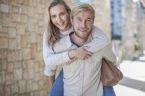 Feliz jovem casal, mulher equitação piggyback — Fotografia de Stock