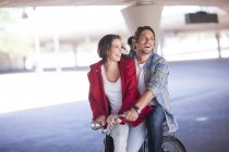 Happy couple riding bicycle in parking garage — Stock Photo