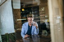 Young man sitting in a bar ooking at his cell phone — Stock Photo