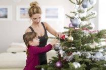Маленька дівчинка, Прикраси Різдвяна ялинка з матір'ю у вітальні — стокове фото