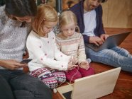 Father using laptop, mother playing with daughters on toy computer on Christmas Eve — Stock Photo