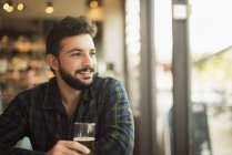 Smiling man sitting in a coffee shop and looking through window — Stock Photo