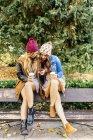 Due migliori amiche utilizzando lo smartphone in parco in autunno — Foto stock