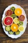 Teller mit Blaubeeren, Kiwis und geschnittenen Zitrusfrüchten auf dunklem Holz — Stockfoto