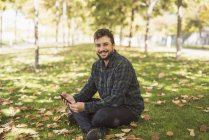 Portrait of smiling man with smartphone sitting on meadow in autumn — Stock Photo