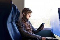 Молода людина сидить в поїзді, дивлячись на планшет — стокове фото