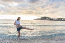 Счастливая беременная женщина стоит на пляже и брызгает водой — стоковое фото