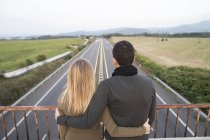 Couple on bridge looking at motorway — Stock Photo