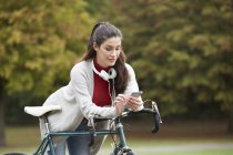 Woman with bicycle in autumnal park text messaging with smartphone — Stock Photo