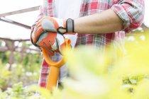 Hands of male gardener holding handle of spade — Stock Photo