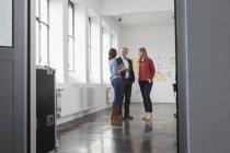 Бізнесмен і дві жінки в офісі говорити — стокове фото