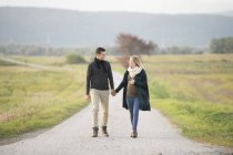 Happy expectant parents walking in rural landscape — Stock Photo